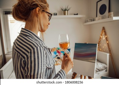 Beautiful artist woman painting in her room while drinking wine.