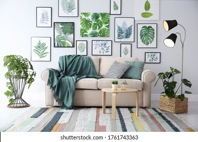Beautiful artworks and comfortable couch in stylish room. Interior design
