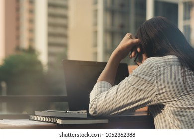 beautiful Asia business woman ,girl working,using computer notebook with serious and unhappy from working .student   tired from work  sitting thinking to something with lonely and powerless.