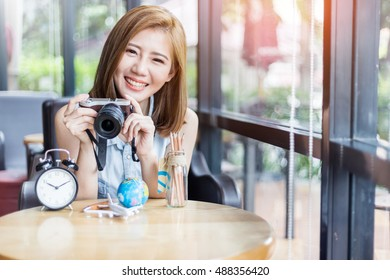 beautiful asia girl with camera with alarm clock plane toy globe in cafe with travel concept light flare effect