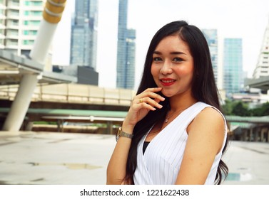 Beautiful Asia girl smile portrait on walking street and building background.
