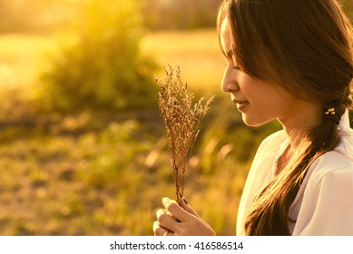 beautiful asia girl stand alone Hold flower in meadow. hope and relaxing on sunset