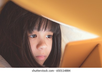 Beautiful Asia small female kid child girl sneaking play tablet computer pc under blanket at night in a dark room. Adorable elementary school girl sneak playing smartphone on her bed in bedroom.