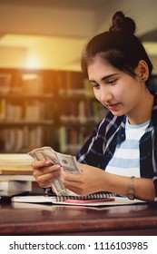 beautiful Asia teen,girl ,student counting Us dollar banknotes money with fun and happy in the library.investment in education concept.