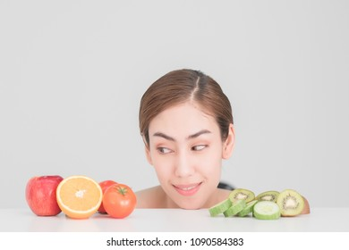 beautiful asia woman with healthy fruits on table, white background,skin care concept