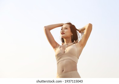 Beautiful Asia woman sexy and smile portrait on beach and soft sunrise on face.