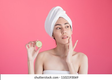 beautiful asia woman with towel on head with perfect clean skin smiling holding cucumber slices over pink background. Beauty cosmetology and spa.