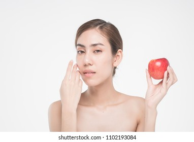 beautiful asia woman with towel on head with perfect clean skin smiling holding apple slices over white background. Beauty cosmetology and spa.
