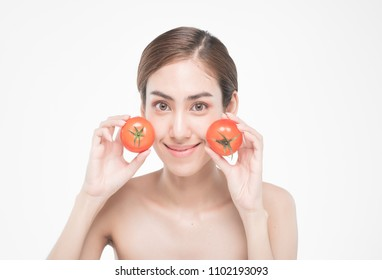 beautiful asia woman with towel on head with perfect clean skin smiling holding tomato slices over white background. Beauty cosmetology and spa.
