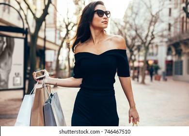 Beautiful asia woman walking on the street with shopping bags.  Trendy female model outdoors in city road with shopping bags.