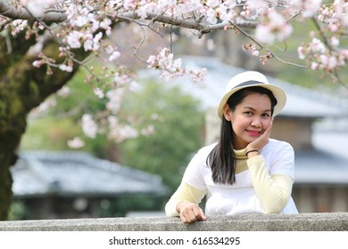 Beautiful Asia woman wear white hat feel relax at Philosopher's path with Pink Sakura full bloom park. The most beautiful flower at Kyoto, Japan.