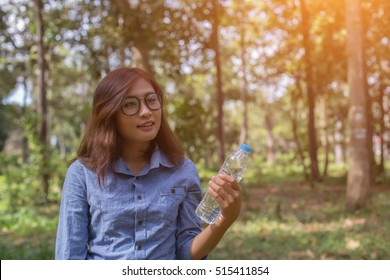 Beautiful asia women sitting drinking water in the forest.