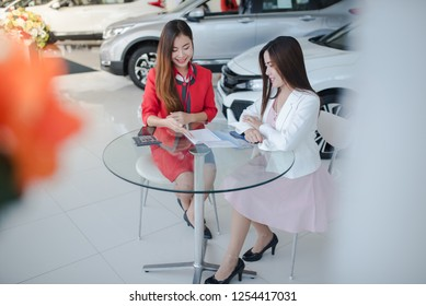 beautiful Asian american woman buying a car at dealership