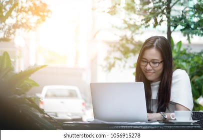 Beautiful asian attractive woman has working and typing on laptop computer for business marketing at coffee cafe in the morning with happy and relaxing time.