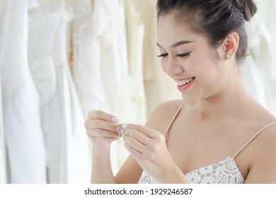 Beautiful Asian bride happy with bridesmaids together help each other to fit elegant lace dress, wedding dress maker try to fit the bride suit in wedding studio or Wedding dress shop store