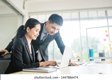 Beautiful asian business man and woman looking in laptop in office and happy, excitng expressing winning gesture.Successful and celebrating victory with business.Teamwork, Close the deal, Promote.
