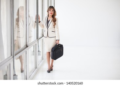 Beautiful Asian Business Woman with a briefcase and her reflection in the glass