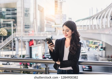 Beautiful Asian business woman smiling and using smart phone outdoor city background. Communication or Social media concept.