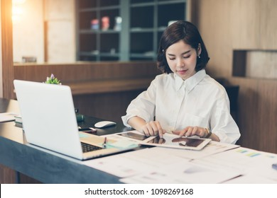 Beautiful asian business woman working on desk with tablet.