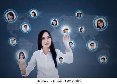 Beautiful Asian businesswoman clicking on digital social network on blue background