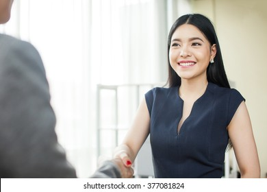 Beautiful Asian businesswoman smiling and shaking hands with other businessman