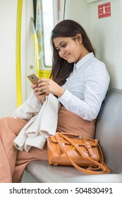 Beautiful Asian businesswoman using smartphone in the LRT Train