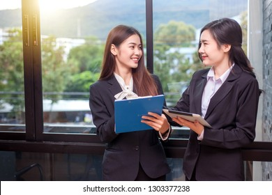 Beautiful asian businesswoman who is standing in the conversation, exchanging ideas at work.