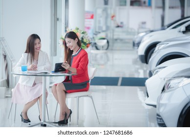 Beautiful Asian car salesman is communicating with customers. To buy a new car
