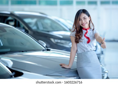 A beautiful Asian car saleswoman is happy to sell a new car in the showroom and enjoy selling the car.