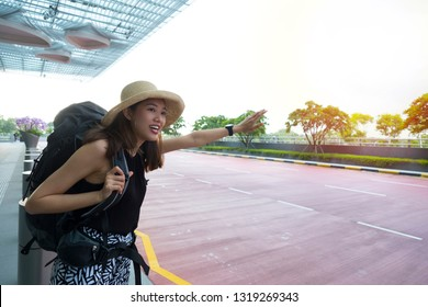 Beautiful asian or caucasian woman tourist with backpacker and straw hat looking for cab or taxi at the airport with sunlight and sky as background. Vacation, travel, taxi, grab and hitchhike concept.