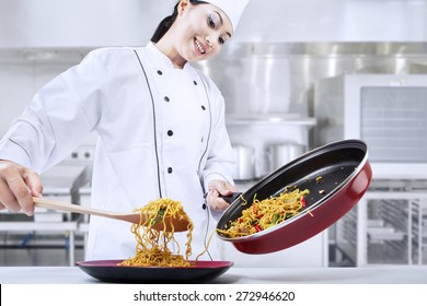 Beautiful asian chef cooks fried noodle in the kitchen