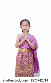 Beautiful Asian child girl in traditional thai dress praying isolated on white background. (Sawasdee is meaning hello).