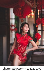 Beautiful Asian Chinese Woman Wearing Cheongsam Traditional Red Dress Siting on Chair Fashion Posting Chinese New Year