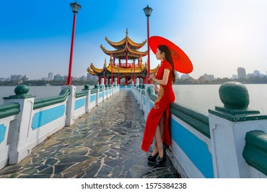 Beautiful Asian Chinese Woman Wearing Cheongsam Traditional Red Dress standing on bridge at Wuliting pavilion,Kaohsiung,Taiwan