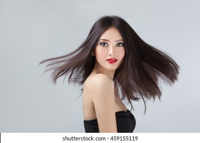 Beautiful asian coasian woman with long hair posing in studio on grey background. Women Hair Is Fluttering In The Wind.