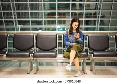 Beautiful Asian college student holding smartphone, waiting for flight at airport, travel or study abroad concept, with copy space.