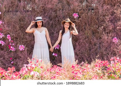 Beautiful Asian couple LGBT women spent time together in park, homosexual announcement relationship in wedding dress for social acceptance, Attractive girlfriend of 2 women hug with love and caring
