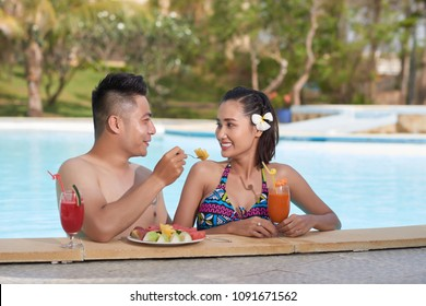 Beautiful Asian couple in love enjoying fresh fruits and drinkins in swimming pool