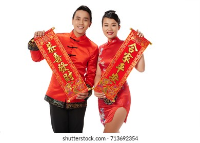 Beautiful Asian couple showing scrolls with Tet couplets to wish you luck