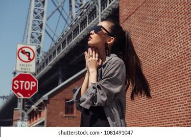 Beautiful asian fashion model girl posing on city street wearing stylish denim clothes and sunglasses.