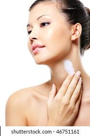 Beautiful asian female  applying cosmetic moisturizer  cream on neck