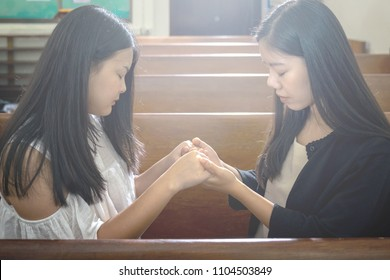 Beautiful Asian Female Couple Praying Together in the Church. Light Filter Added.