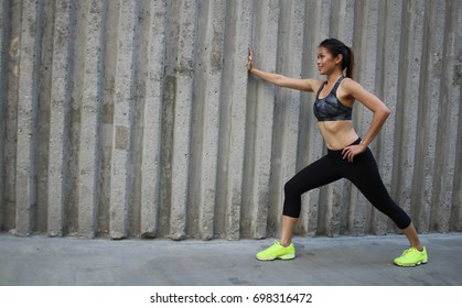 Beautiful Asian female doing stretching exercises against a concrete wall