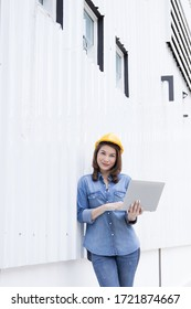 Beautiful Asian female engineer in jeans dress wearing yellow safety hard hat using laptop computer notebook doing job at construction site outside office. Idea for modern working woman.
