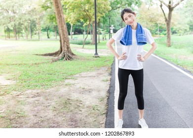 beautiful Asian female exercise in public park, she warm up to prepare jogging, she relax and smile on nature background, health promotion