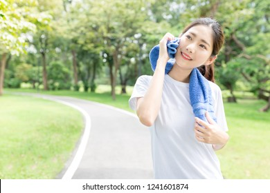 beautiful asian female exercise in public park, she absorb sweat with her towel, she relax and smile on nature background, health promotion