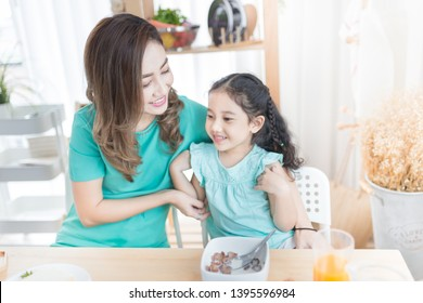 beautiful asian female  hug her daughter, they sitting on chair and feeling happy in family time, mother's day,  child health promotion and child development