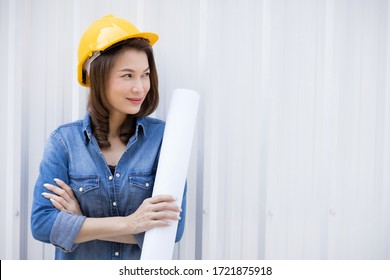 Beautiful Asian female in jeans dress wearing yellow safety hat and holding roll of white paper plan standing in front of metal sheet wall at construction site outside office. Idea for working woman.