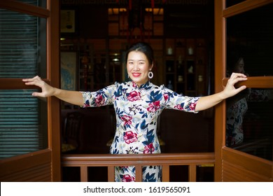Beautiful Asian female opening window with a huge smile.China lady wearing qipao in traditional setting.Happy woman with red lipstick during festival. Chinese New Year celebration.