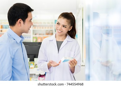 Beautiful Asian female pharmacist or doctor explaining prescription medicine to a male customer in a pharmacy.